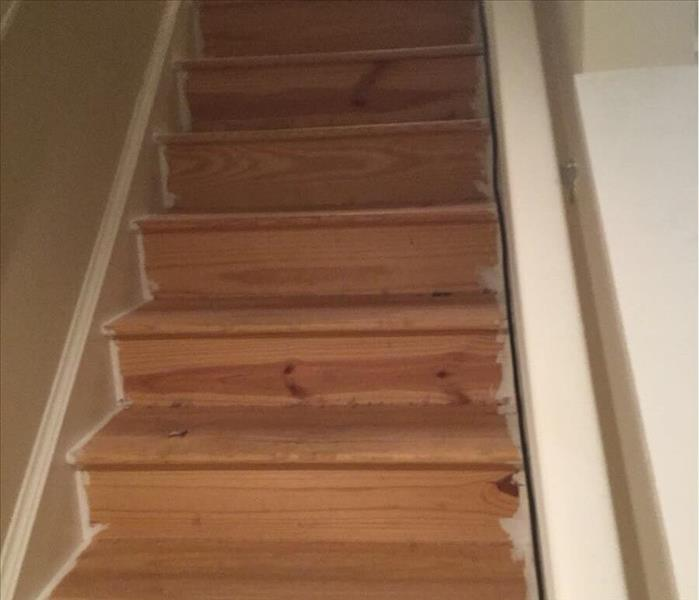Light brown wood stairs in a stairway with tan walls and white trim.