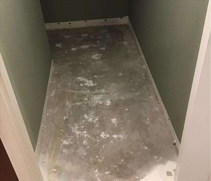 Concrete floor in a closet with green walls and white trim.