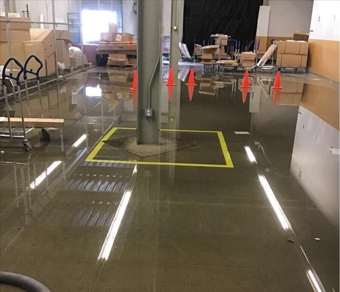 Wet floor in a warehouse with orange cones and brown boxes in the background.
