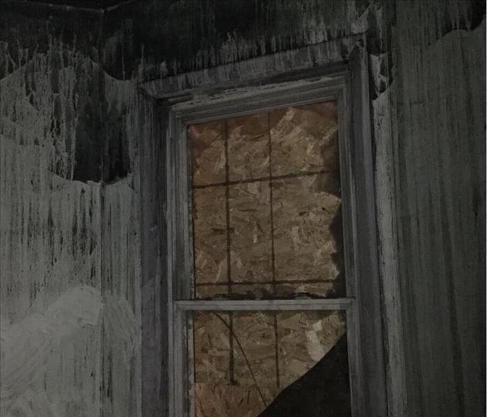 A room with walls covered in soot with a boarded up window.
