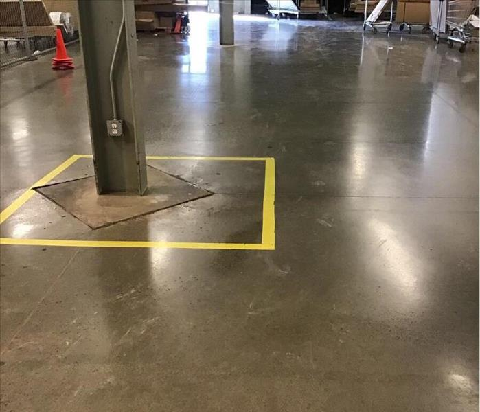 Dry floor of a warehouse with a yellow square around a support beam in the background.