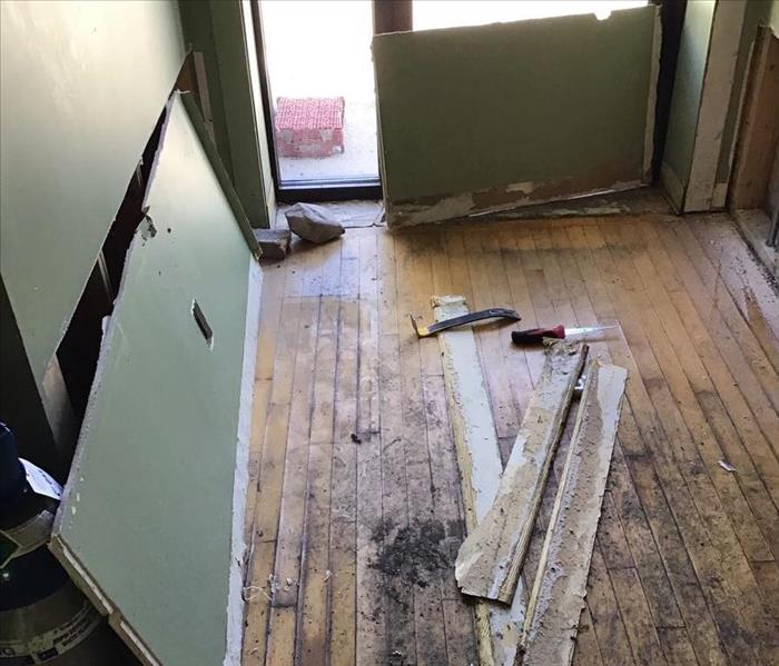 Wood floor with soot and debris on the floor of an entry way with a glass door.