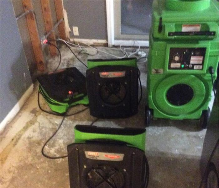 Green dehumidifier and three air blowers set up on a kitchen floor.