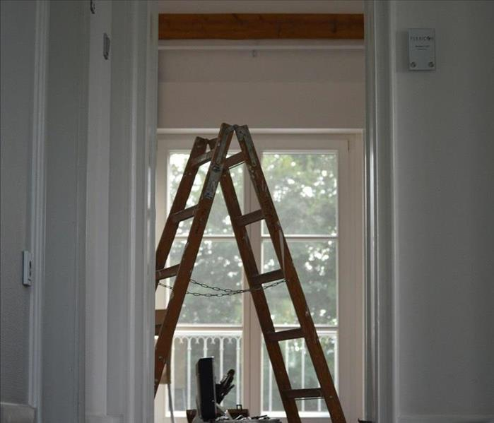 White bedroom with a brown ladder in front of a window.