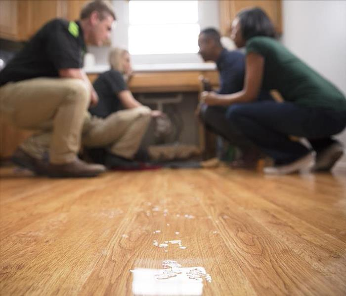 Wet wood floor with SERVPRO employees talking to customers while kneeling on the floor.