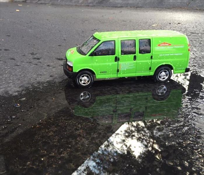 Green SERVPRO van on a wet road.