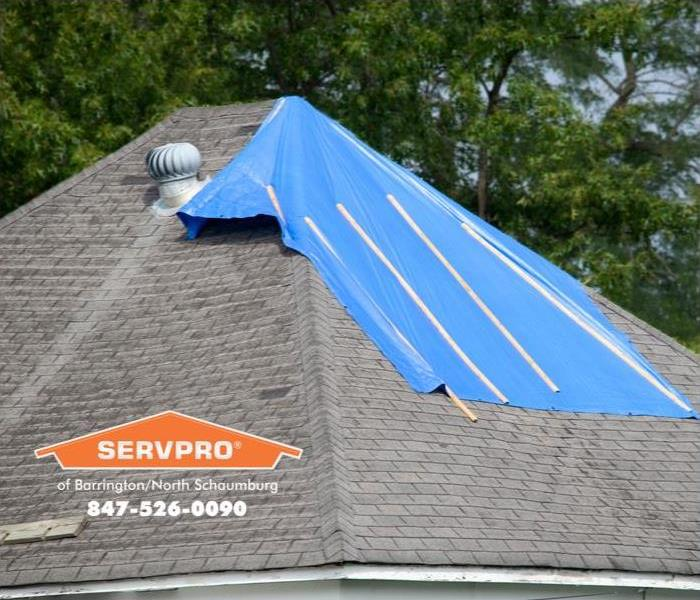 Tarp covering water damage on the roof of a Lake Zurich home.