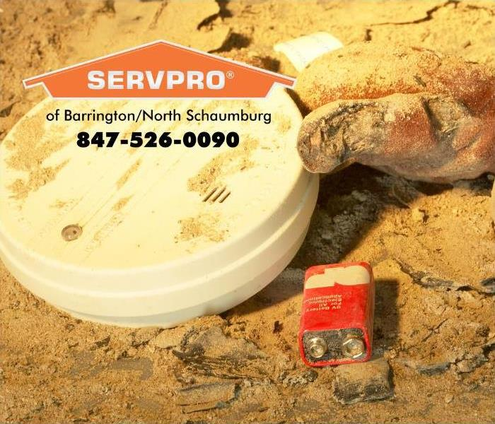 A smoke detector covered in ashes from fire damage, with a new battery laying next to it.